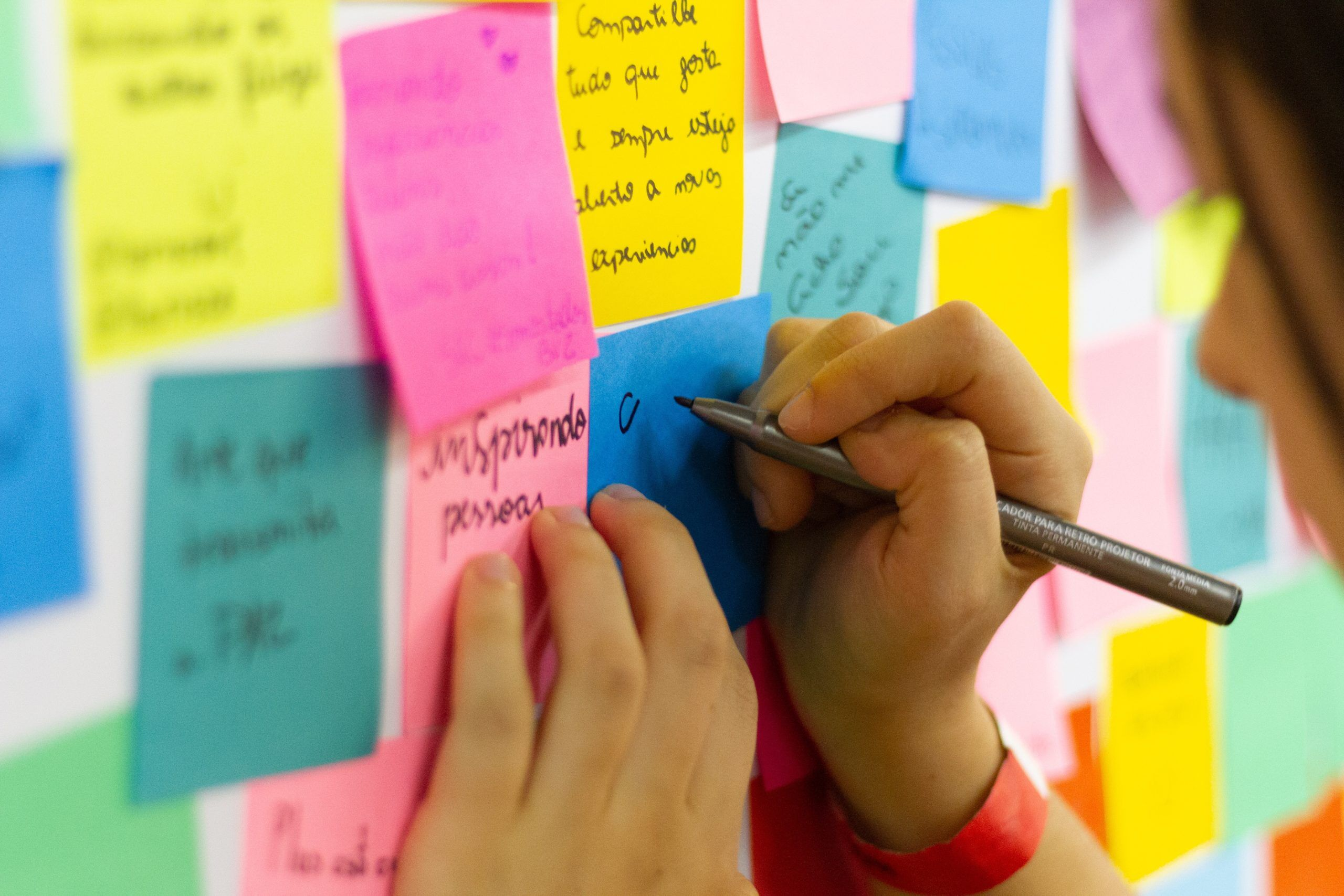 person-writing-on-pink-sticky-notes-3854816